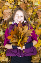 Portrait of laughing girl lying on the ground holding bunch of autumn leaves - SARF002266