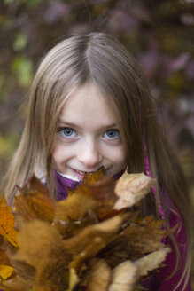 Portrait of girl holding bunch of autumn leaves - SARF002269