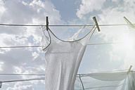 Laundry hanging on clothesline in sunlight - RIBF000347