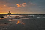 Germany, Schleswig-Holstein, North Sea Coast, View of Westerheversand Lighthouse, tideland at sunrise - KEBF000258