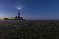 Germany, Schleswig-Holstein, North Sea Coast, View of Westerheversand Lighthouse at night - KEBF000267