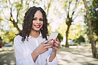 Portrait of smiling young woman with brown ringlets and red lips with smartphone - RAEF000612