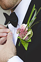 Groom with buttonhole flowers buttoning his shirt - GEMF000458