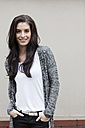 Portrait of smiling young woman with hands in her pockets - GDF000885