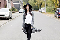 Portrait of smiling young woman wearing black hat walking on a street - GDF000888