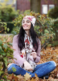 Portrait of young woman wearing autumn fashion hearing music with earphones - GDF000894