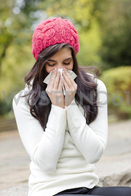 Young woman wearing red woolly hat blowing her nose - GDF000897