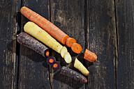 Three different sorts of sliced carrots on dark wood - CSF026592