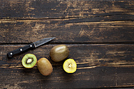 Whole and sliced different kiwis and a knife on dark wood - CSF026631