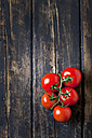 Bunch tomatoes on dark wood - CSF026637