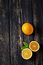 Sliced and whole orange on dark wood - CSF026640