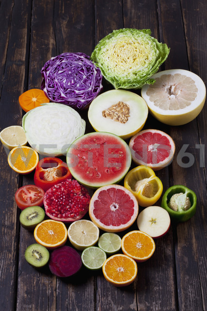 Halves of different vegetables and fruits on dark wood - CSF026670