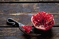 Sliced pomegranate and a knife on dark wood - CSF026676