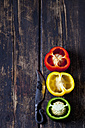 Three halves of red, yellow and green bell pepper and a knife on dark wood - CSF026679