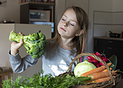 Portrait of girl with wickerbasket of fresh vegetables looking at broccoli - SARF002284