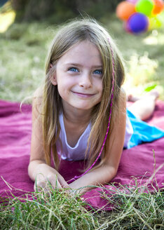 Portrait of smiling little girl lying on blanket on a meadow - SARF002290