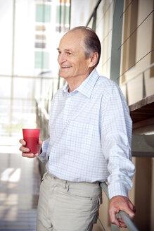 Laughing senior leaning on railing - RMAF000162