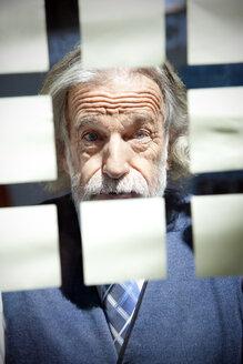 Senior businessman writing on adhesive notes - RMAF000165