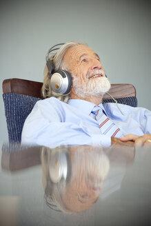 Senior man wearing headphones, listening music - RMAF000180