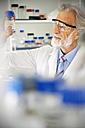 Senior professor looking at laboratory glass - RMAF000186
