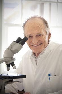 Professor in laboratory examining samples under microscope - RMAF000195