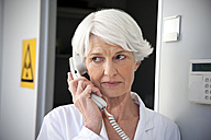 Senior woman working at laboratory making a call - RMAF000198