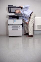 Senior man putting head in copying machine - RMAF000204