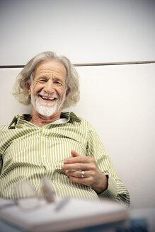Laughing senior man leaning on wall, portrait - RMAF000210