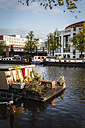 Netherlands, Amsterdam, Houseboat at Amstel river with Het Muziektheater in background - EVGF002491