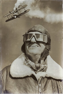 Portrait of acrobatics pilot and flying biplane in the background - KLR000267