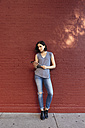 Portrait of woman with digital tablet leaning against red brick wall - GIOF000385