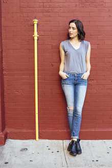 Portrait of woman with hands in her pockets leaning against red brick wall - GIOF000388