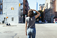 USA, New York City, back view of young woman standing on a street - GIOF000394