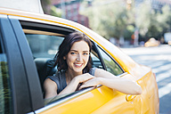 USA, New York City, portrait of smiling young woman sitting inside of yellow cab - GIOF000406