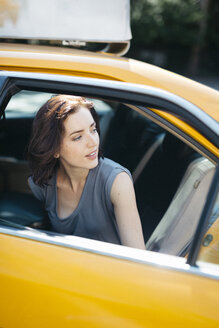 USA, New York City, portrait of  young woman getting on a yellow cab - GIOF000409