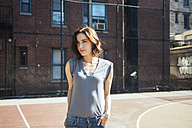 USA, New York, Manhattan, portrait of young woman standing on a playground - GIOF000412