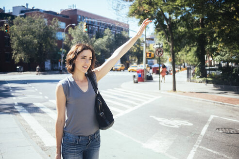 USA, New York City, young woman hailing a taxi - GIOF000421
