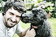 Poodle licking the face of his owner in the garden - JATF000758