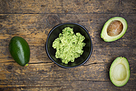 Bowl of Guacamole and whole and sliced avocados on dark wood - LVF004104