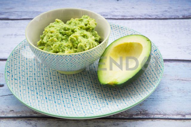 Bowl of Guacamole and half of an avocado on a plate - LVF004110