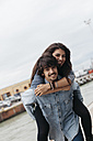 Italy, Rimini, young man carying girlfriend piggyback - GIOF000447