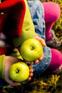 Little girl holding two green apples, close-up - LVF004116