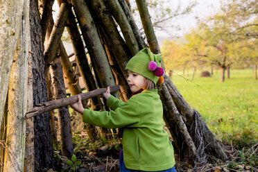 Little girl building a hut with logs on a meadow in autumn - LVF004119