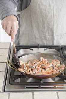 Man frying shrimps in pan - ECF001820