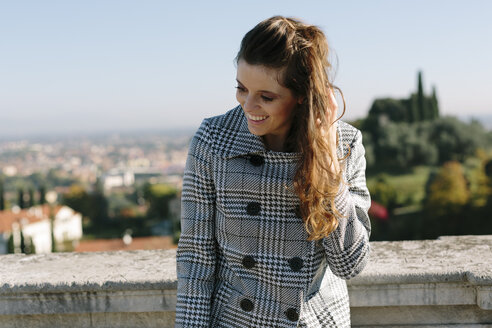 Italy, Vicenza, smiling brunette woman in checkered coat - GIOF000454