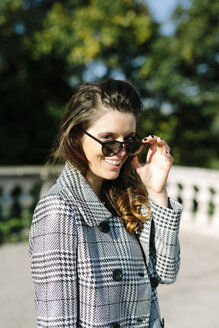 Italy, Vicenza, smiling brunette woman wearing checkered coat and sunglasses - GIOF000463