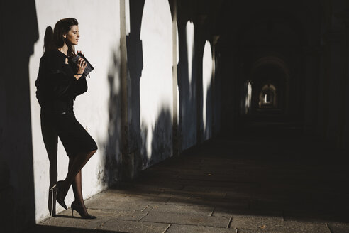 Young woman standing against a wall in an arcade - GIOF000466