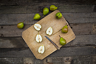 Whole and sliced Bonne de Longueval with kitchen knife on wooden board and dark wood - LVF004141
