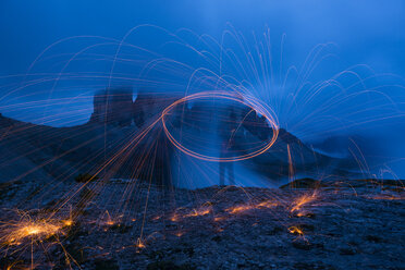 Italy, Alto Adige, Dolomites, hiker making light trails in front of Tre Cime di Lavaredo by night - LOMF000072