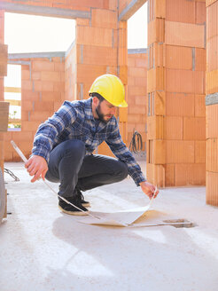 Foreman with construction plan and pocket rule at construction site - LAF001539